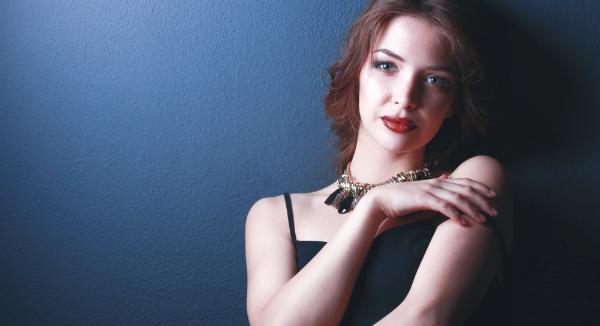 Schoene Frau mit Abend-Make-up im schwarzen Kleid