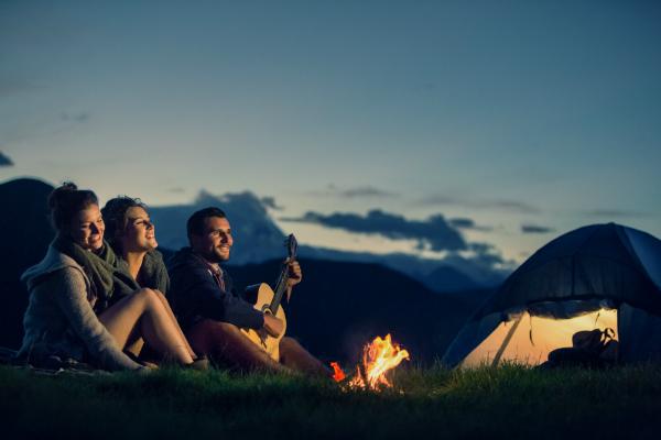 Drei Freunde campen mit einer Gitarre vor dem Lagerfeuer