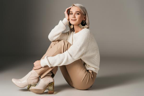 Elegante modische Frau posiert in weissem Pullover und Heels