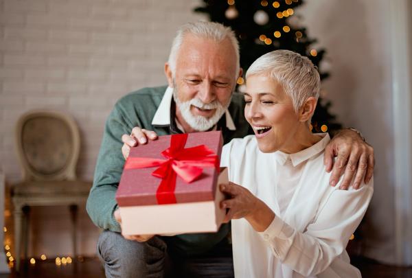 Aelterer Mann gibt seiner Frau ein Weihnachtsgeschenk