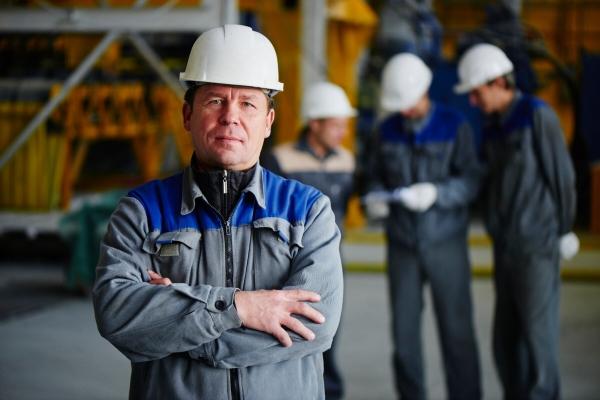 Arbeiter traegt Overall und Helm