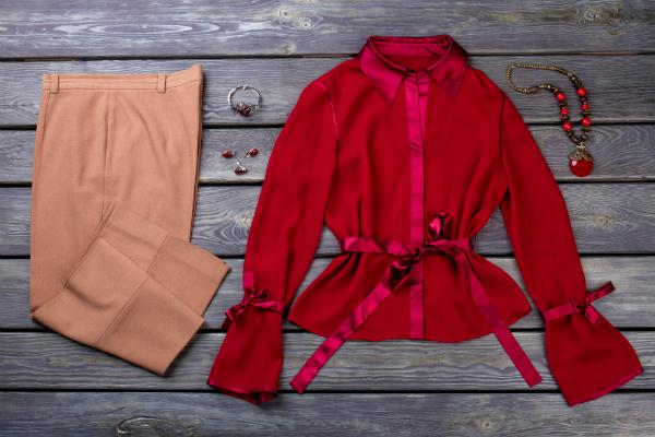 Braune Damenhose und rote Bluse mit Schmuck