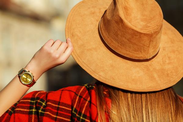Frau mit hellbraunem Hut aus Wildleder und goldener Armbanduhr