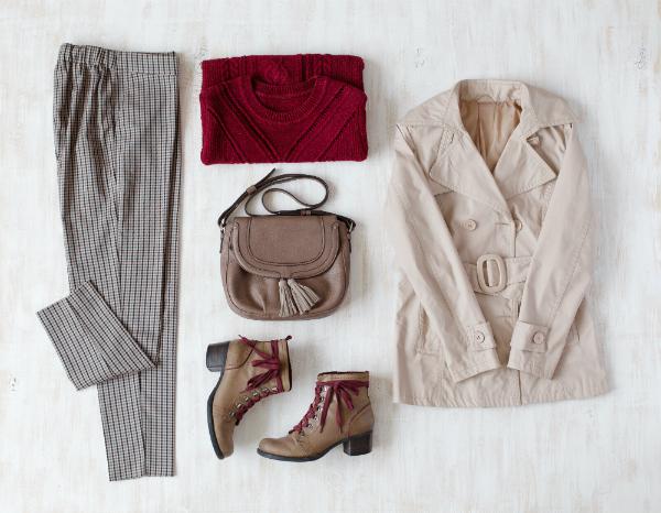 Karierte Hose, dunkelroter Oversize-Strickpullover, kleine braune Ledertasche, braune Lederstiefeletten, beiger Mantel