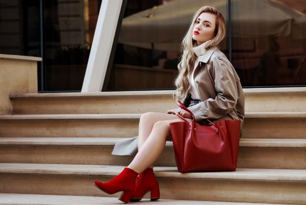 Modische Frau mit beigem Trenchoat und roten Stiefeletten