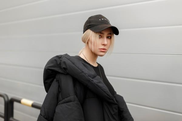 Stilvolles junges Maedchen mit einer modernen schwarzen Snapback und Winterjacke