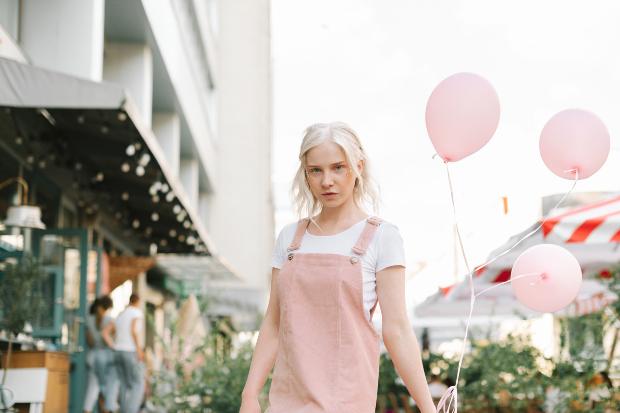 Junge Frau in pinkfarbigen Kleid: Streetwear wird femininer - Röcke und Kleider sind im Trend