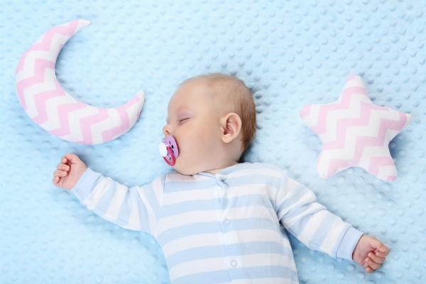 Schlafendes Baby mit Spielsachen im Bett