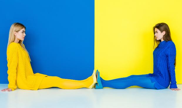 2 junge Frauen, eine in Blau, eine in Gelb - Kleiden im All-Over-Look