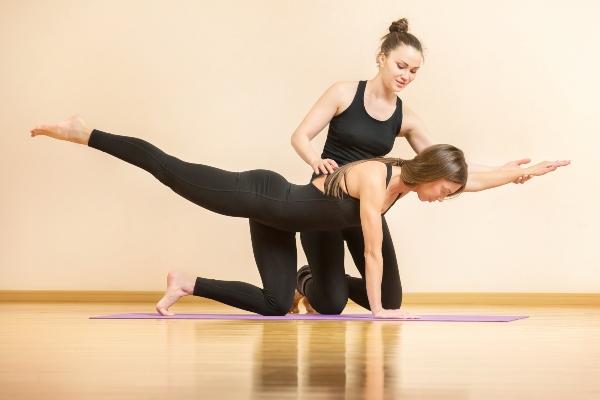 Yogalehrerin hilft Frau Asana-Posen yoga-outfit