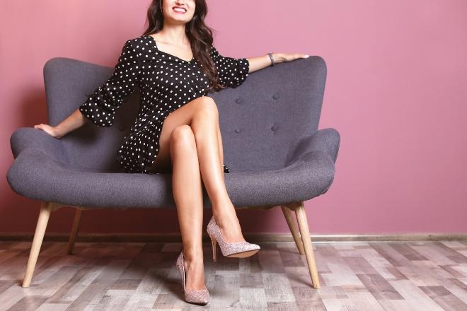 Junge Frau sitzt auf Sofa mit Hiigh Heels und Kleid