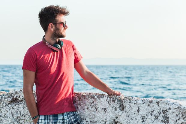 Mann mit rotem T-Shirt am Meer