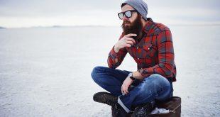 Junger Mann in Holzfällerhemd und Jeans