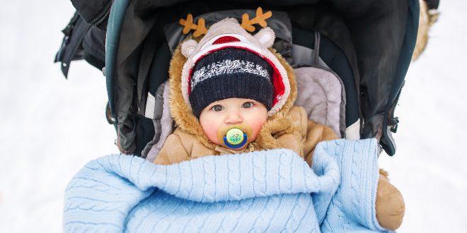 Baby im Kinderwagen in Babykleidung im WInter