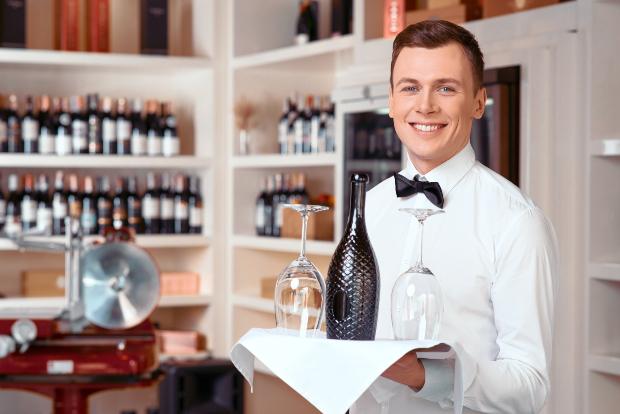 Junger Kellner: Koch und Kellner Kleidung repräsentiert das Unternehmen