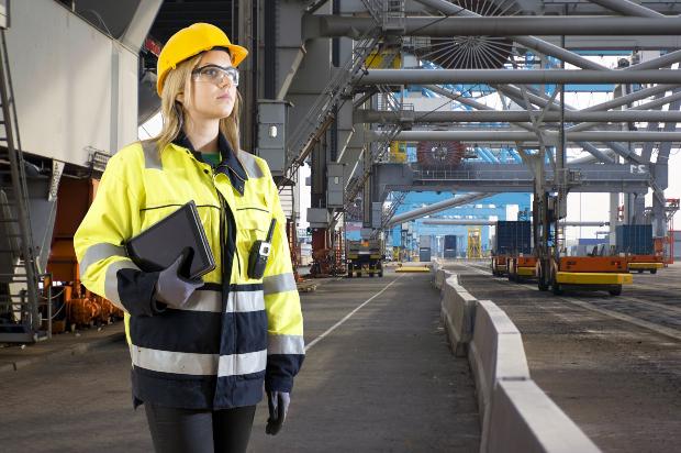 Frau in Sicherheitsjacke, mit Helm und Handschuhen und Sicherheitsbrille