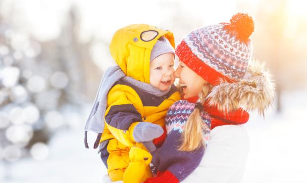 Fröhliche Mutter mit fröhlichem Kleinkind in Winterkleidung