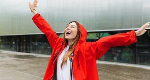 Junge Frau lächelnd im Regen - Regenfeste Kleidung modisch kombiniert