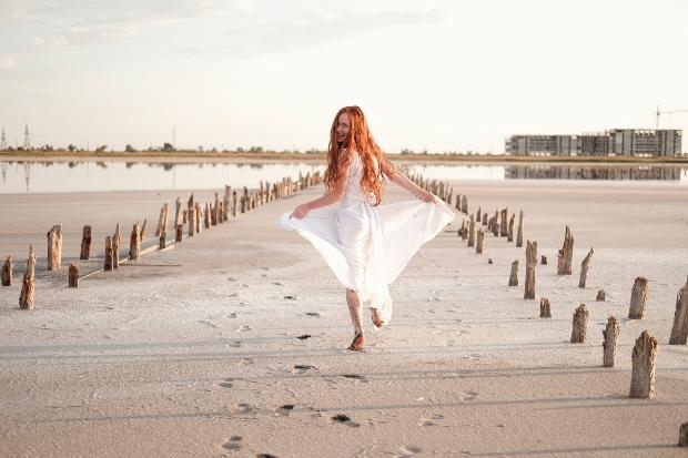 Dame im weißen Kleid am Strand