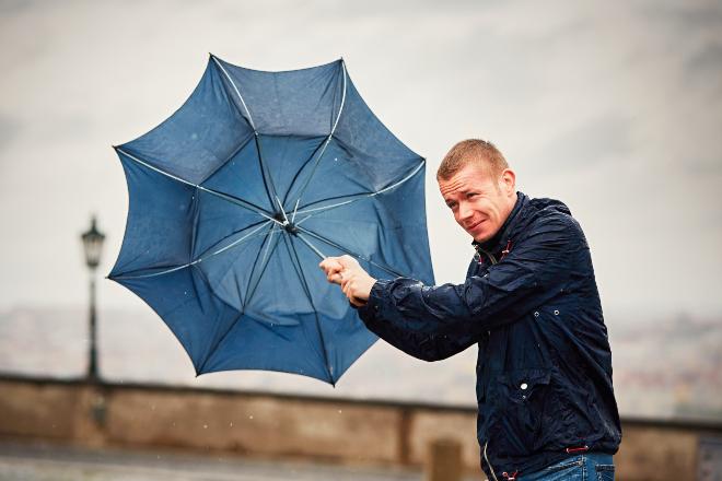 Mann mit Regenschirm im Wind - Ideale Schlechtwetterkleidung sieht anders aus