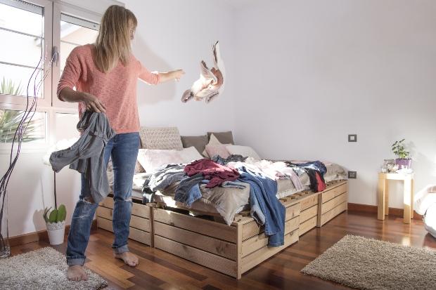 Frau wirft Kleidung auf einen Haufen