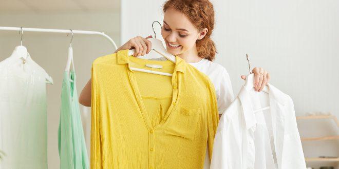 Junge Frau wählt unterschiedliche Basic-Kleidungsstücke aus, die an einem Kleiderständer hängen