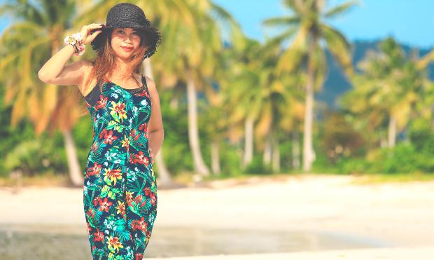 Junge Frau am Strand mit blumigem Outfit