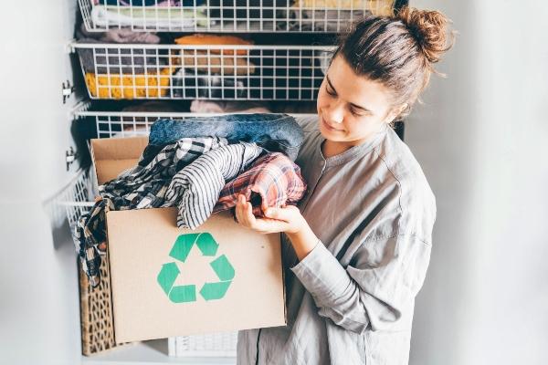 Junge Frau mit voller Kleidung der Recyclingbox