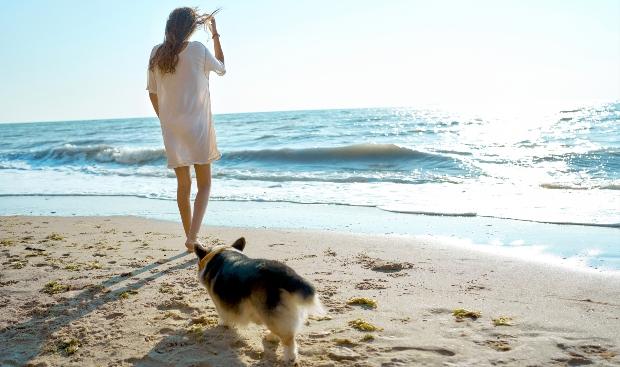 Frau im T-Shirt-Kleid und mit Hund am Strand
