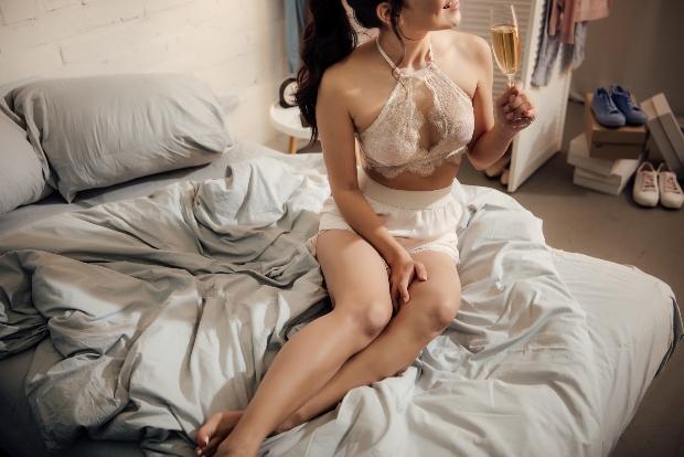 Junge Frau im Bralette und mit Sektglas in der HAnd