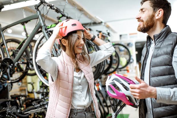 Junger Mann und junge Frau im Radladen, tragen beide eine Sportweste