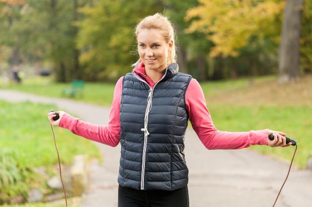 Frau beim Seilspringen mit Sportweste