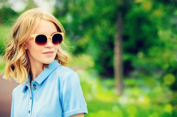 Junge Frau mit Sonnenbrille und kurzem Hemd - Was zeichnet gute Freizeithemden aus?