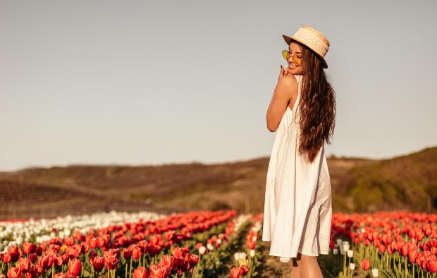 Junge Frau in weißem leichten Kleid steht im Blumenfeld - Sommertrends der Mode 2020