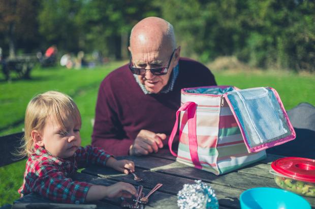 Großvater mit Enkelin sitzen am Tisch in einem Park mit einer Kühltasche