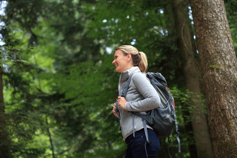 Glueckliche Frau beim Wandern im Wald