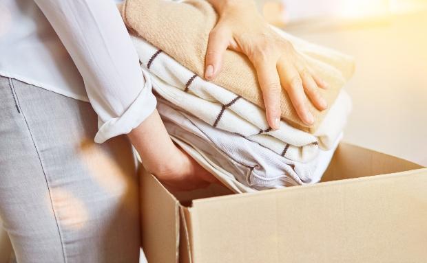Frau packt Kleidung in eine Kiste