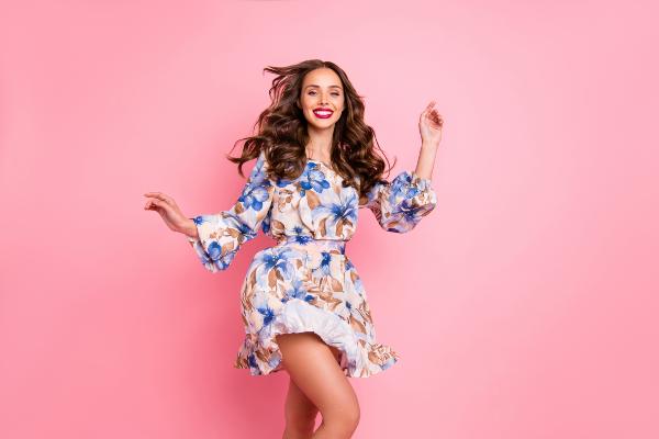 Junge Frau in einem Sommerkleid mit floralen Ornamenten - verspielte Mode