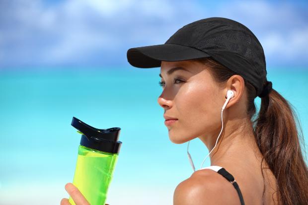 Eine junge Frau mit Schildkappe und Träger-Top genießt die Sonne