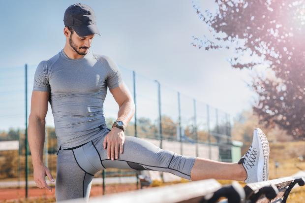 Ein sportlicher Mann in Running-Wear dehnt sein Bein an einer Parkbank