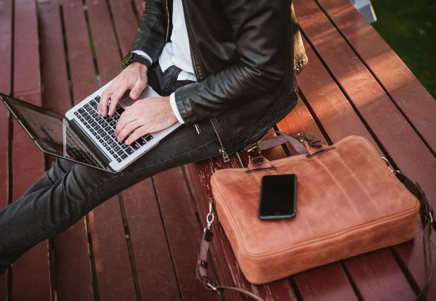Ein Mann sitzt auf einer Bank auf benutzt sein Laptop, neben Ihm liegt eine schicke Notebooktasche