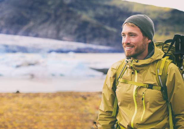 Ein junger Mann mit Rucksack, Outdoorjacke und Mütze wandert bestens gerüstet einen Berg hinauf