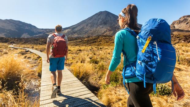 Ein junger Mann und eine junge Frau wandern über einen Steg auf einen Berg in der Ferne zu