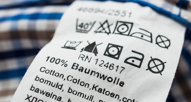 """Ein Schild mit Pflege- und Waschhinweisen für ein T-Shirt auf dem """"100% Baumwolle"""" steht T-Shirt kaufen"""
