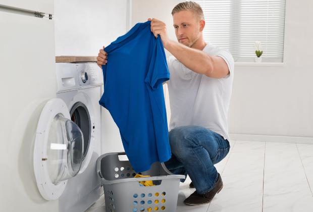 Ein Mann ist dabei, T-Shirts und weitere Kleidungsstücke in die Wäschetrommel zu geben