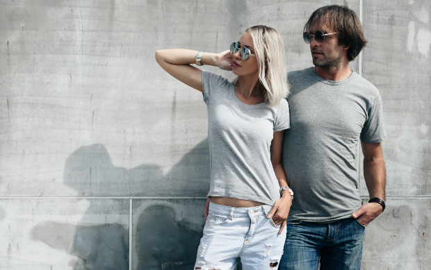 Ein Paar in T-Shirt und Jeans steht vor einer Hauswand