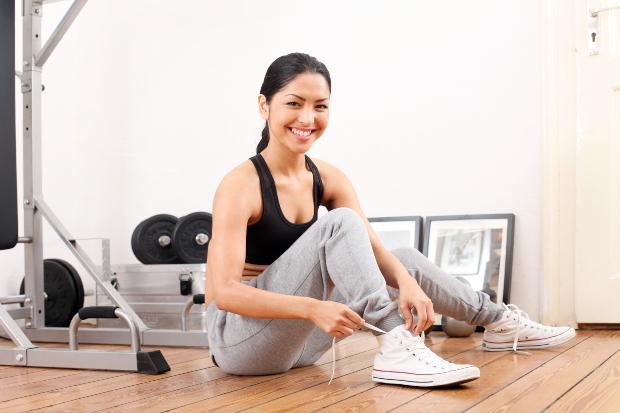 Eine junge Frau in Sweathose bereitet sich auf die Trainingseinheit im Home-Gym vor Sweathosen