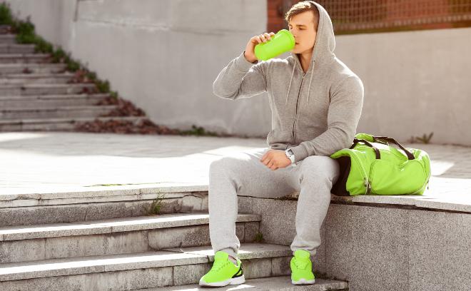 Ein athletischer junger Mann in modischer Sportbekleidung nimmt einen Schluck aus seiner Trinkflasche Sweathosen