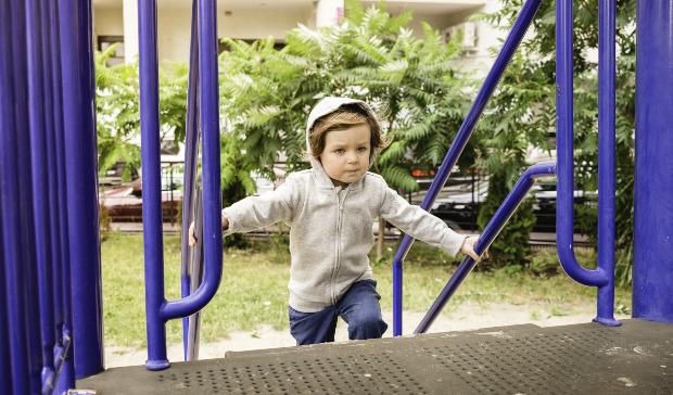 Kind mit Hoodie spielt auf Treppe - Kindergartenkleidung
