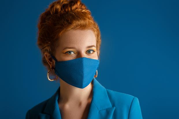 Junge Frau trägt blauen Mund-Nasen-Schutz